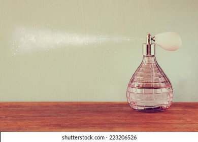 vintage antique bottle with effect of perfume spray, on wooden table. retro filtered image