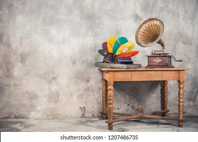 Vintage antique brass gramophone phonograph turntable and colorful vinyl discs in aged special holder suitcase on oak wooden table front concrete wall background. Retro old style filtered photo