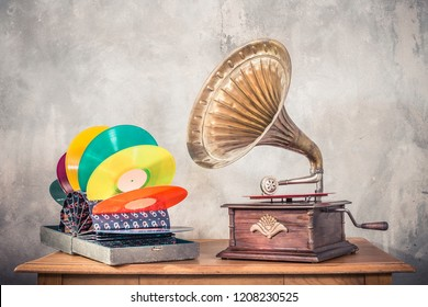 Vintage antique gramophone phonograph turntable with brass horn and colorful vinyl discs in aged special holder suitcase on wooden table front concrete wall background. Retro old style filtered photo
