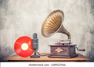 Vintage antique gramophone phonograph turntable with brass horn, studio microphone and red color vinyl discs on wooden table front concrete wall background. Retro old style filtered photo