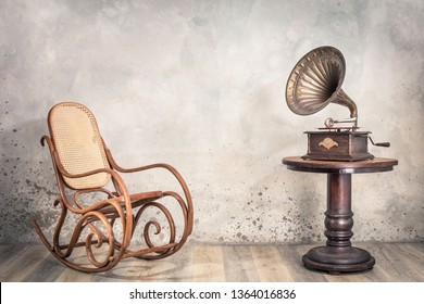 Vintage antique gramophone phonograph turntable with brass horn on wooden table and aged rocking chair front concrete wall background with shadow. Retro old style filtered photo