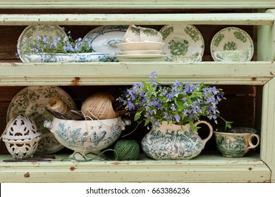 Vintage, antique kitchen items on very old aged, weathered wooden shelf, bouquet of wild flowers in faience pitcher, shabby chic style