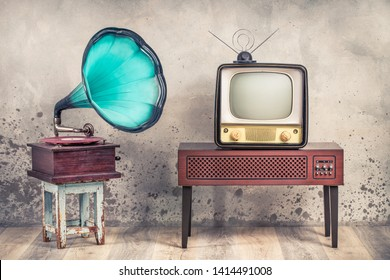 Vintage antique mint blue gramophone phonograph turntable on aged stool and old television from 50s on wooden TV stand front grunge textured loft concrete wall background. Retro style filtered photo