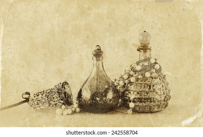 vintage antique perfume bottles, on wooden table. retro filtered image.  Old style photo.