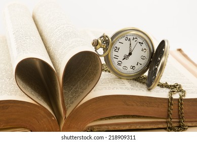 Vintage antique pocket watch and heart of the book's pages