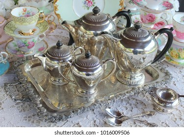 Vintage antique silver tea set on a tray with tea cups and saucers, high tea party