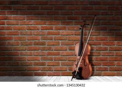 Vintage antique violin near brick wall background.