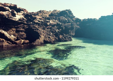 Vintage Aperture filter background picture of a black, rocky cliff and clear turquoise water