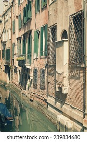 Vintage appearance of Venice side streets with typical facade, canal and motor boat. Several filters applied.