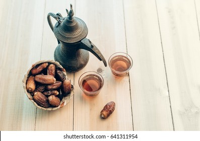 A vintage arabian coffee pot- a Dallah and sweet dates. A rustic set up of middle eastern food photography.