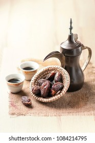 Vintage arabic coffee pot, black coffee and dates. The rustic Middle Eastern food photography.