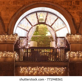 Vintage arched window with balcony at night decorated with many shining Christmas lights