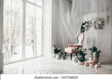 vintage armchair decorated with flowers and greens, stands in a classic room on a white wooden floor surrounded by lighted candles near  large window and curtains