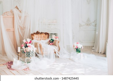 vintage armchair decorated with peonies  flowers and greens, stands in a classic room on a white wooden floor surrounded by candles near large window and curtains