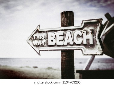 Vintage artistic color arrow shaped sign showing way to the beach, on the pole on the beach, sea background.