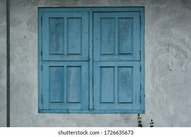 Vintage asian old wooden blue window with grunge texture wall