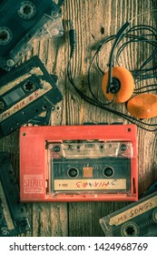Vintage audio cassette, headphones and walkman on wooden table