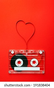 Vintage audio cassette with loose tape shaping a heart on red background
