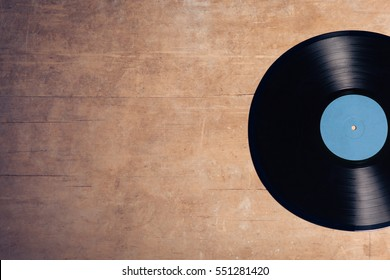 vintage audiophile and musiclover set; vinyl musical disc on wooden background;