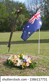 Vintage Australian Army 303 rifle, a soldier's dogtags, iconic Aussie slouch hat (clearly showing the rising sun badge) and a floral wreath with Australian National Flag in background on ANZAC Day.
