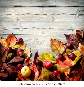 Vintage Autumn border from apples and fallen leaves on old wooden table/Thanksgiving day concept/background with apples