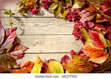 Vintage Autumn border from ashberry and and fallen leaves on old wooden table/Thanksgiving day concept