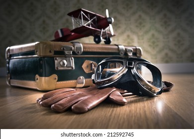 Vintage aviator equipment on the floor with glasses, gloves and toy plane.