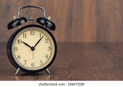 Vintage background with alarm clock on a table