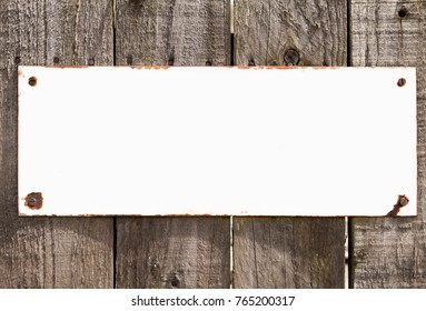 Vintage background  with blank rustic white metal sign screwed to weathered wood background.