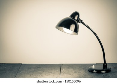 Vintage background with lighting retro desk lamp on wood table