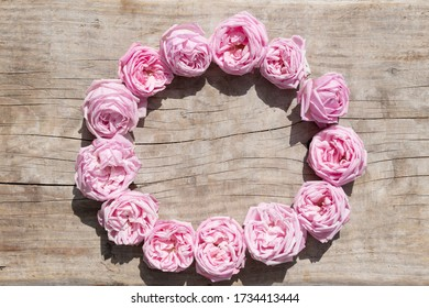 Vintage background pink roses in wreath on a wooden board
