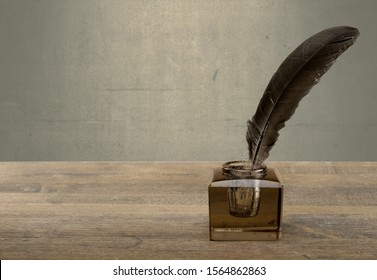 Vintage background with quill pen and inkwell on table