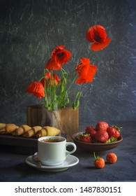 Vintage background with red poppies in a wooden vase, a cup of coffee, strawberries in a plate and croissants on a wooden tray