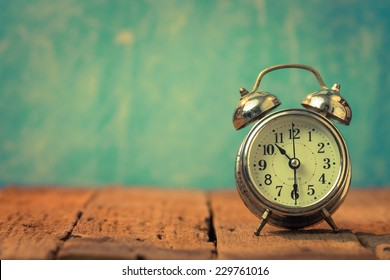 Vintage background with retro alarm clock on table
