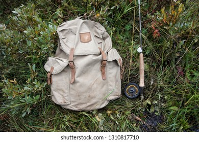 Vintage backpack and fly rod with reel and fly.