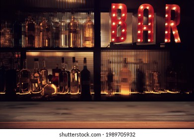 Vintage BAR sign with lights in the dark with bottles of alcohol and a wooden empty tabletop.