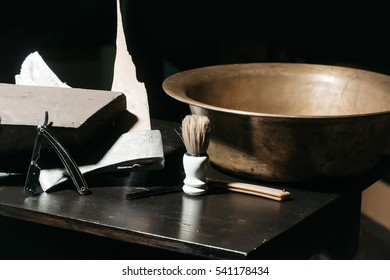 Vintage barber or shaver tools on wooden table. Old razors with blades, copper basin, shaving brush, broken axe and towel on dark background