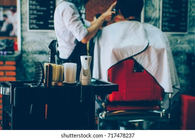 Vintage barber shop accessories with a young Asian man getting a haircut by a hairdresser in the background. Vintage tone concept.