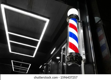 vintage Barbershop window pole. Old-fashioned barber pole in the window, night shot, selective focus.