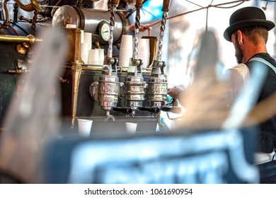 Vintage barista prepare coffee to customer in old style machine with handmade retro look and throwback clothes in an outdoor market stall