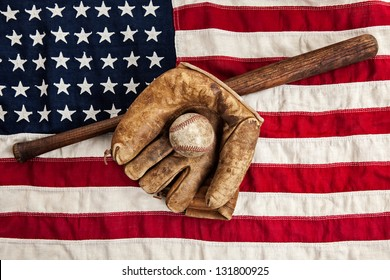 Vintage baseball bat, glove and ball on a vintage American flag