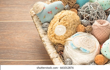 Vintage basket white color handicraft on wooden background. A dark background. Various beads, ribbons, heart, textiles, nuts. Materials for art and craft
