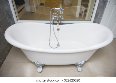 vintage bathtub with faucet and shower in bathroom, interior