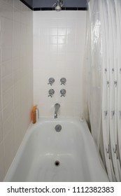 A vintage bathtub and shower with selective focus on the four handles, two for the tub and two for the shower