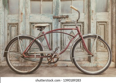 Vintage beach cruiser bicycle in front of antique wooden weathered doors