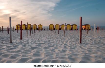 Vintage beach huts on the Belgian coast at sunset