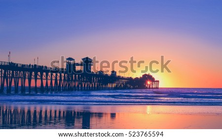 Vintage beach photo of pier at sunset in California