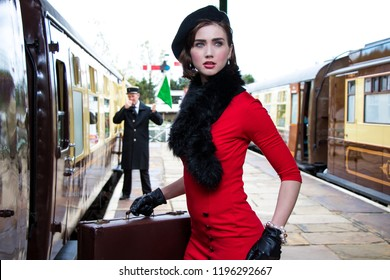 Vintage beautiful female wearing red dress and black beret carrying suitcases as she boards train at train station