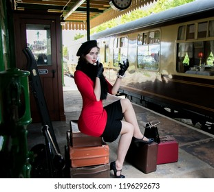Vintage beautiful female wearing red dress and black beret, sitting on suitcases, looking in mirror and applying her lipstick.