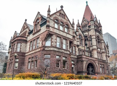 A vintage beautiful old historic building on a cool overcast autumn day in downtown Toronto, Canada, with it's two tone brown brick and stone finish, with tall turrets and arched entrance.